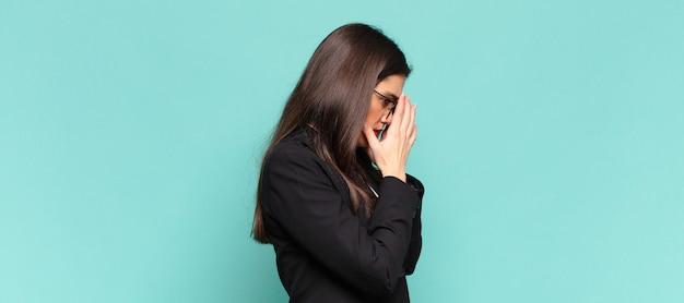 Młoda ładna kobieta zakrywająca oczy rękami ze smutnym, sfrustrowanym wyrazem rozpaczy, płaczu, widok z boku. pomysł na biznes