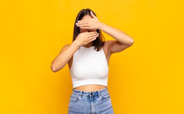 """Młoda ładna kobieta zakrywająca twarz obiema rękami, mówiąc """"nie"""" do aparatu! odmawianie zdjęć lub zakaz zdjęć"""
