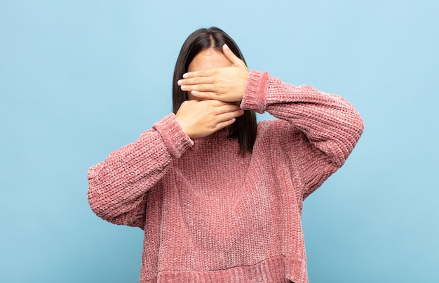 Młoda ładna kobieta zakrywająca twarz obiema rękami, mówiąc nie! odmawianie zdjęć lub zakaz zdjęć