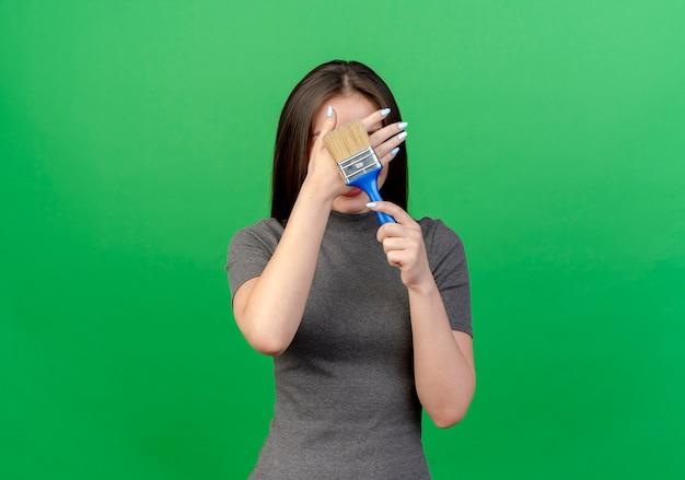 Młoda ładna kobieta zakrywająca twarz ręką i trzymając pędzel na białym tle na zielonym tle z miejsca na kopię