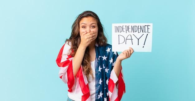Młoda ładna kobieta zakrywająca usta rękami z koncepcją zszokowanego dnia niepodległości