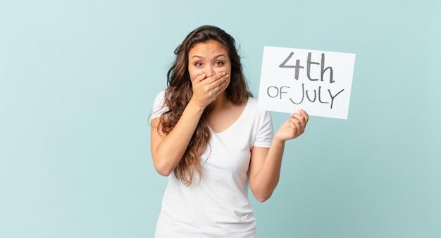 Młoda ładna kobieta zakrywająca usta rękami z zszokowaną koncepcją dnia niepodległości