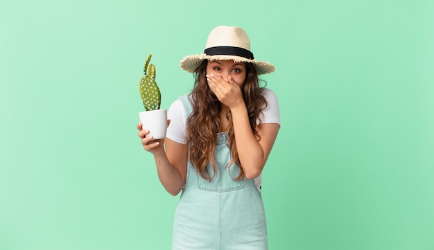 Młoda ładna kobieta zakrywająca usta rękami zszokowana i trzymająca kaktusa