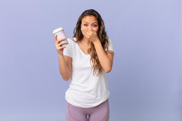 Młoda ładna kobieta zakrywająca usta rękami zszokowana i trzymająca kawę