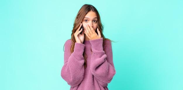 Młoda ładna kobieta zakrywająca usta rękami zszokowana i używająca smartfona