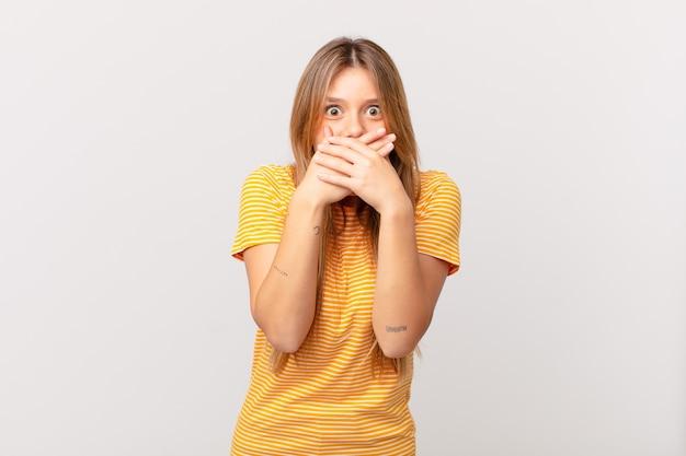 Młoda ładna kobieta zakrywająca usta rękami zszokowana