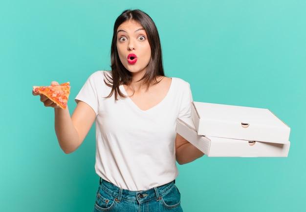 Młoda ładna kobieta zaskoczona wyrazem twarzy i trzymająca pizzę