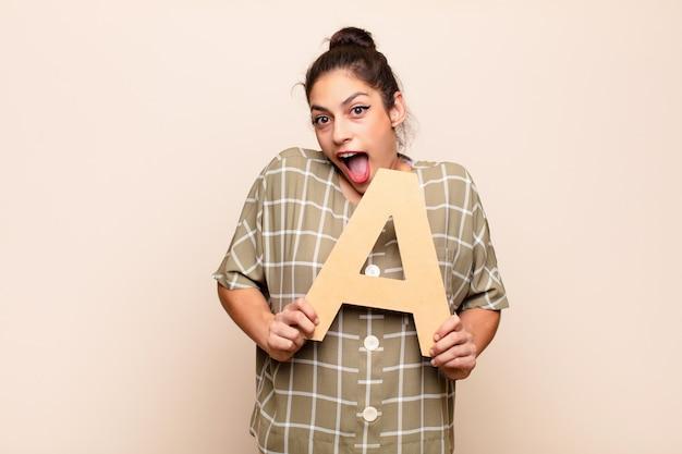 Młoda ładna kobieta zaskoczona, zszokowana, zdziwiona, trzymając literę a alfabetu, aby utworzyć słowo lub zdanie.