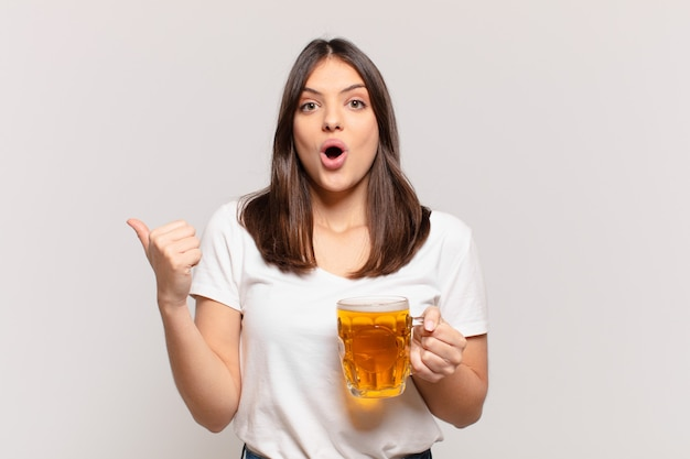 Młoda ładna kobieta zaskoczony wypowiedzi i trzyma piwo