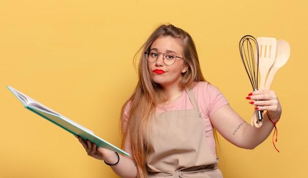 Młoda ładna kobieta zdezorientowana koncepcja gotowania szefa kuchni