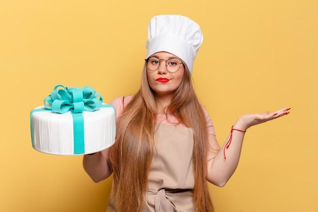 Młoda ładna kobieta zdezorientowana koncepcja tort urodzinowy wyrażenie