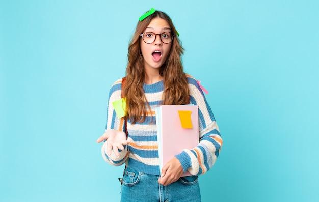 Młoda ładna kobieta zdumiona, zszokowana i zdumiona niesamowitą niespodzianką z torbą i trzymającą książki
