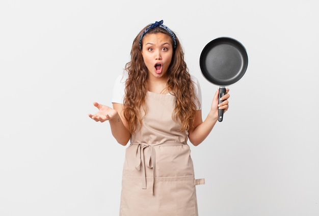 Młoda ładna kobieta zdumiona, zszokowana i zdumiona niewiarygodną koncepcją szefa kuchni z niespodzianką i trzymającą patelnię