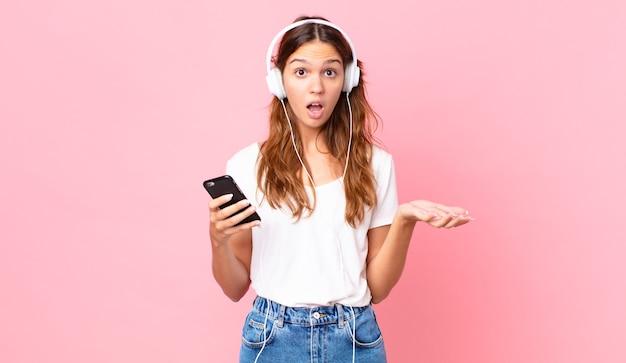 Młoda ładna kobieta zdumiona, zszokowana i zdumiona niewiarygodnym zaskoczeniem ze słuchawkami i smartfonem