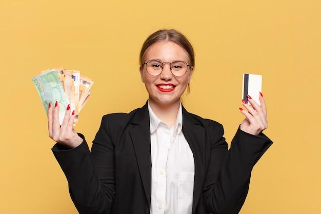 Młoda ładna kobieta ze szczęśliwym i zdziwionym wyrazem twarzy trzymająca pieniądze