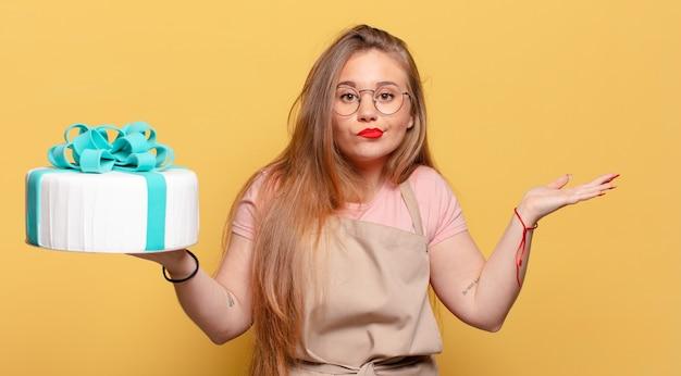 Młoda ładna kobieta ze zdezorientowanym wyrazem twarzy i tortem urodzinowym