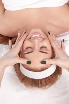 Młoda ładna kobieta zgłosiła się do salonu kosmetycznego i konsultuje się z kosmetyczką w zakresie zabiegów przeciwstarzeniowych