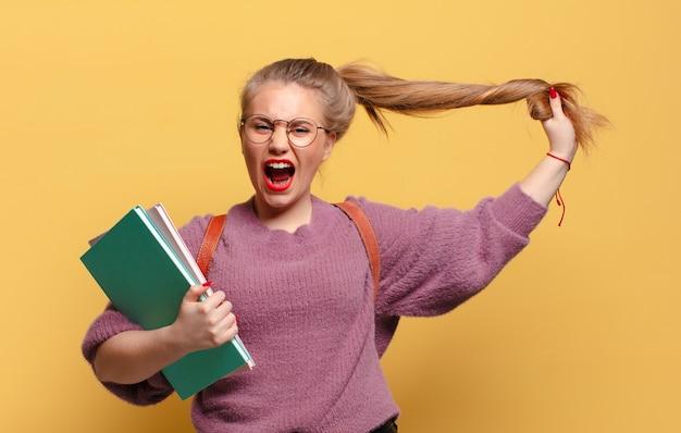Młoda ładna kobieta zły i znudzony wyraz. koncepcja studenta