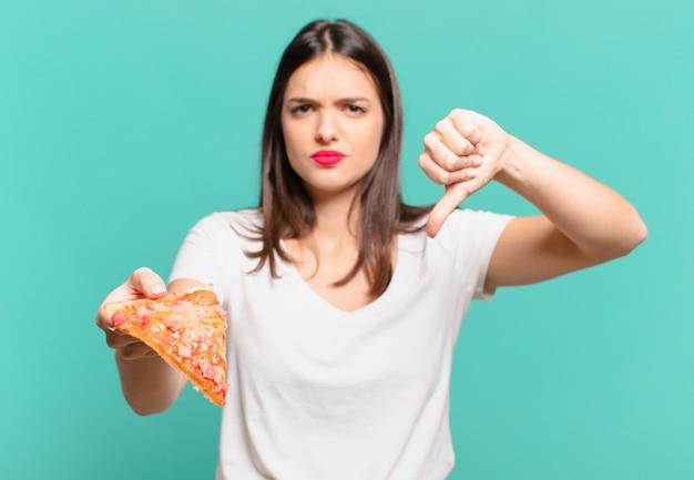 Młoda ładna kobieta zły wyraz twarzy i trzymająca pizzę