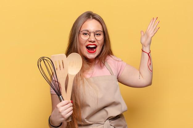 Młoda ładna kobieta. zszokowana lub zdziwiona koncepcja gotowania szefa kuchni