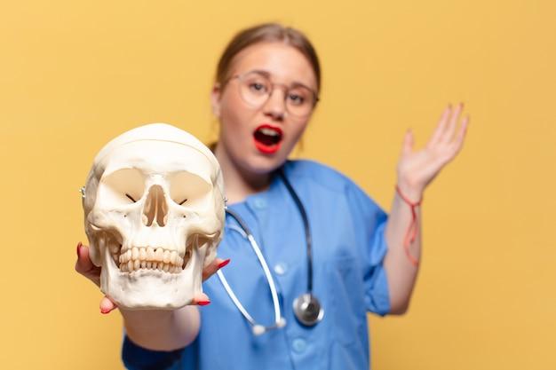 Młoda ładna kobieta. zszokowana lub zdziwiona koncepcja pielęgniarki z wyrazem twarzy