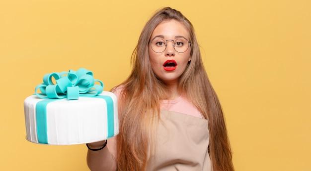 Młoda ładna kobieta. zszokowany lub zaskoczony wyraz twarzy trzymający tort urodzinowy
