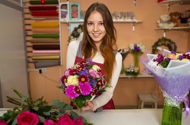 Młoda ładna kobiety kwiaciarnia trzyma bukiet podczas gdy stojący przy kramem kwiatu sklep
