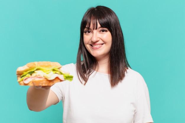 Młoda ładna krągła kobieta jest szczęśliwa i trzyma kanapkę