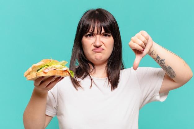 Młoda ładna krągła kobieta z gniewnym wyrazem twarzy i trzymająca kanapkę