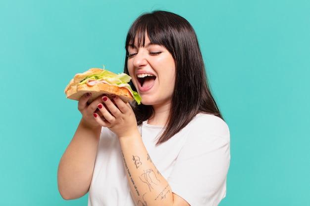 Młoda ładna krągła kobieta zaskoczyła wyrazem twarzy i trzyma kanapkę