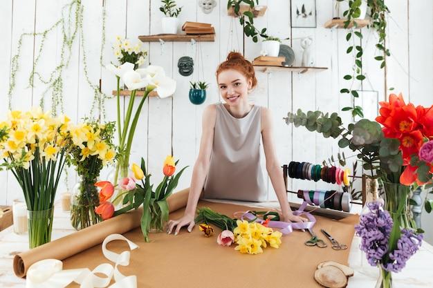 Młoda ładna kwiaciarnia stoi blisko stołu z kwiatami