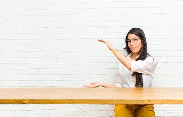 Młoda ładna łacińska kobieta ono uśmiecha się, czuje się szczęśliwy, pozytywny i zadowolony, trzymający przedmiot lub pojęcie na copyspace obsiadaniu lub pokazuje, siedzący przed stołem