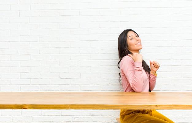 Młoda ładna łacińska kobieta ono uśmiecha się radośnie i od niechcenia wskazujący kopiować przestrzeń na stronie, czując się szczęśliwy i zadowolony siedząc przed stołem