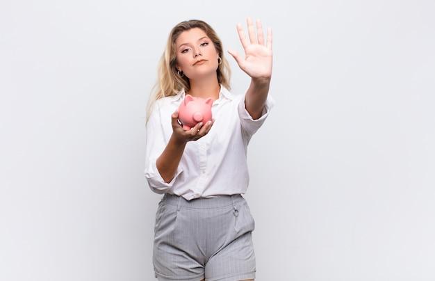 Młoda ładna łacińska kobieta patrzeje poważnego robi przerwa gestowi z piggybank przeciw biel ścianie