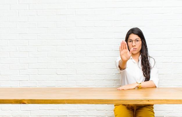 Młoda ładna łacińska kobieta patrzeje poważnego, surowego, niezadowolonego i gniewnego pokazywać otwartą dłoń robi przerwie gestykulować obsiadanie przed stołem