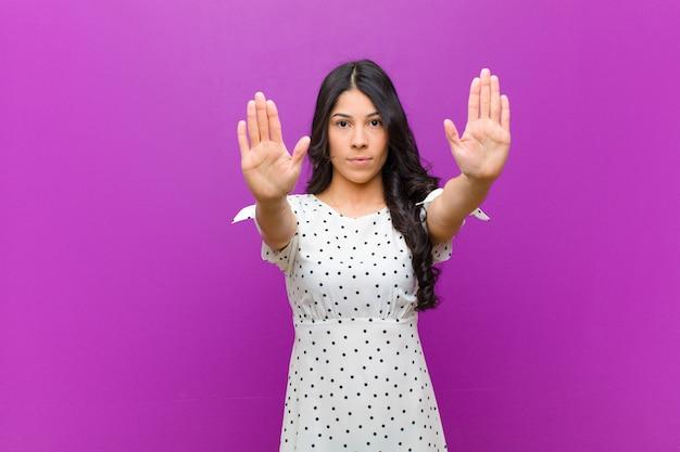 Młoda ładna łacińska kobieta patrzeje poważny z oba otwartymi palmami przeciw purpury ścianie