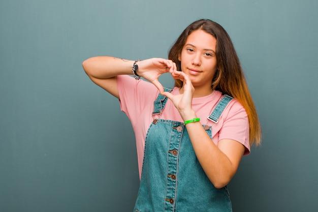 Młoda ładna łacińska kobieta uśmiecha się i czuje się szczęśliwa, słodka, romantyczna i zakochana, tworząc kształt serca obiema rękami na ścianie grunge