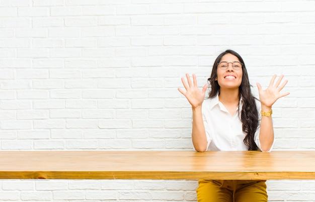 Młoda ładna łacińska kobieta uśmiechnięta i patrzeje życzliwy seans liczba dziesięć lub dziesiąta z ręką do przodu odliczanie w dół