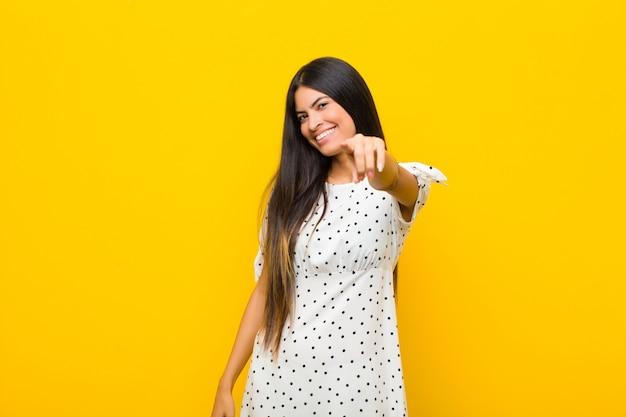 Młoda ładna łacińska kobieta wskazuje z zadowolonym, pewnym siebie, przyjaznym uśmiechem, wybierając ciebie przy płaskiej ścianie