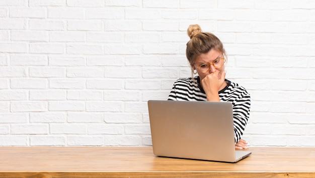 Młoda ładna latynoska czująca się poważnie, zamyślona i zatroskana, wpatrująca się w bok z ręką przyciśniętą do brody, siedząca z laptopem
