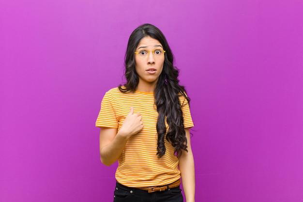 Młoda ładna latynoska czująca się zdezorientowana, zdziwiona i niepewna, wskazująca na zastanawianie się i pytająca, kto, ja? przed fioletową ścianą