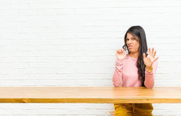 Młoda ładna latynoska czująca się zniesmaczona i mdłości, cofająca się przed czymś nieprzyjemnym, śmierdzącym lub śmierdzącym, mówiąca fuj, siedząca przed stołem