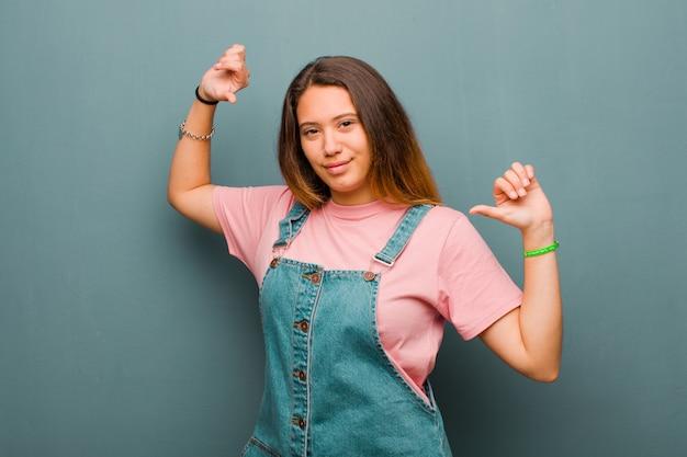 Młoda ładna latynoska czuje się dumna, arogancka i pewna siebie, wygląda na zadowoloną i odnoszącą sukcesy, wskazując na siebie na tle grunge ściany