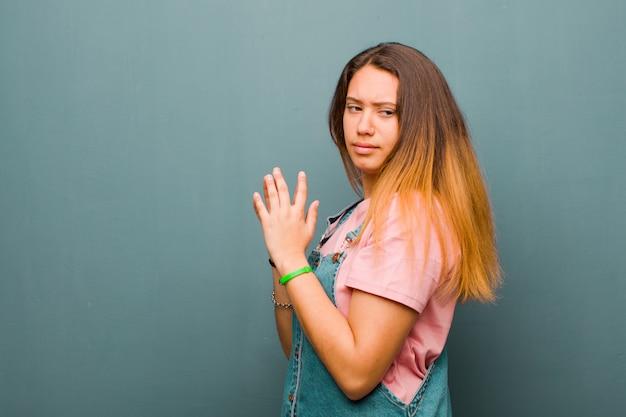 Młoda ładna latynoska czuje się dumna, złośliwa i arogancka, gdy knuje zły plan lub myśli o sztuczce przeciwko ścianie grunge