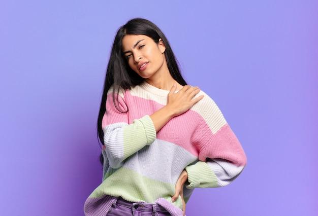 Młoda ładna latynoska kobieta czuje się zmęczona, zestresowana, niespokojna, sfrustrowana i przygnębiona, cierpi z powodu bólu pleców lub szyi