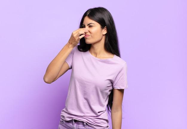 Młoda ładna latynoska kobieta czuje się zniesmaczona, trzyma nos, żeby nie czuć cuchnącego i nieprzyjemnego smrodu