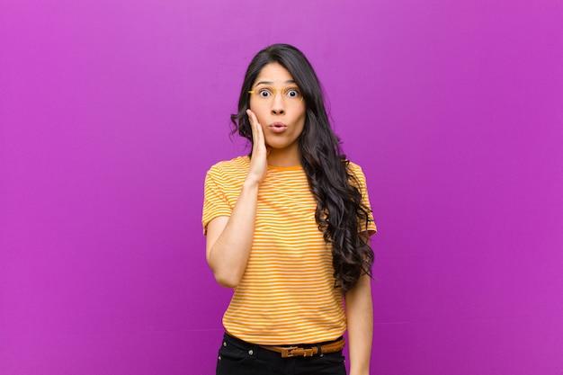 Młoda ładna latynoska kobieta czuje się zszokowana i zdziwiona, trzymając się twarzą w rękę z niedowierzaniem z szeroko otwartymi ustami na fioletowej ścianie