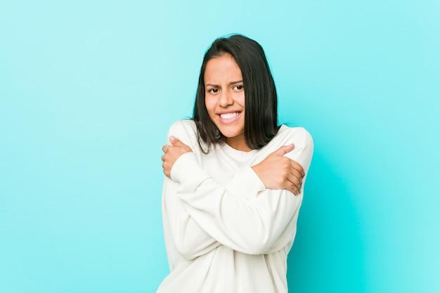 Młoda ładna latynoska kobieta marznie z powodu niskiej temperatury lub choroby.