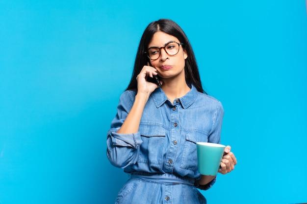 Młoda ładna latynoska kobieta pijąca kawę