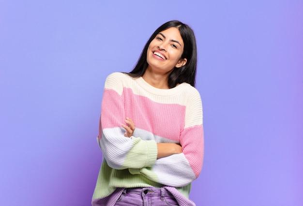 Młoda ładna latynoska kobieta śmiejąca się radośnie ze skrzyżowanymi rękami